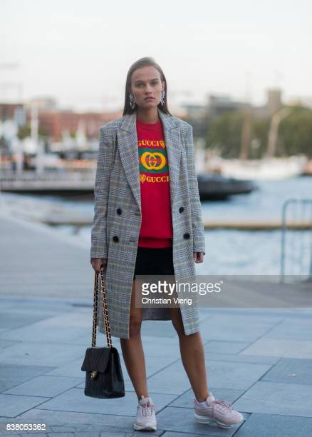 Lisa Alexandra wearing red Gucci sweater Aix Max sneaker black Chanel bag black skirt plaid coat outside Mayow on August 23 2017 in Oslo Norway