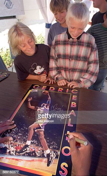 Lisa Anderson and her brother Nate look on as Cedric Ceballos of the Los Angeles Lakers autographs a poster of himself while at Jano Graphics in...