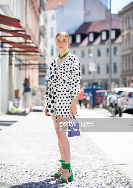 Lisa Banholzer is seen wearing print with dots print Mother of Pearl shoes Fabienne Chapot and purple Medea bag during Mercedes Benz Fashion Week...