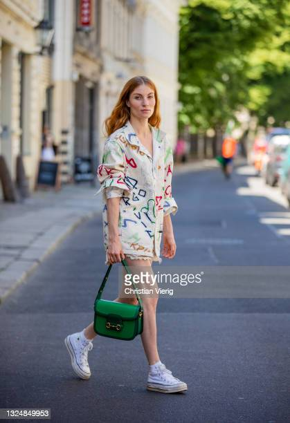 Lisa Banholzer is seen wearing shirt with print Vans X Zodiak, Shorts Levis, shoes Converse, green bag Gucci on June 21, 2021 in Berlin, Germany.