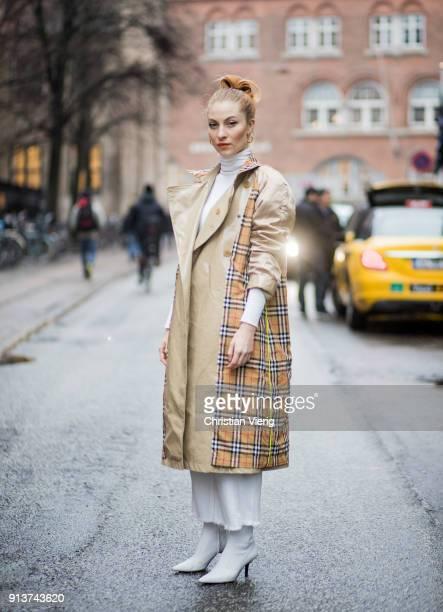 Lisa Banholzer wearing Burberry trench coat white Max Mara turtleneck white Mango boots white wide leg cropped Mango pants is seen during the...