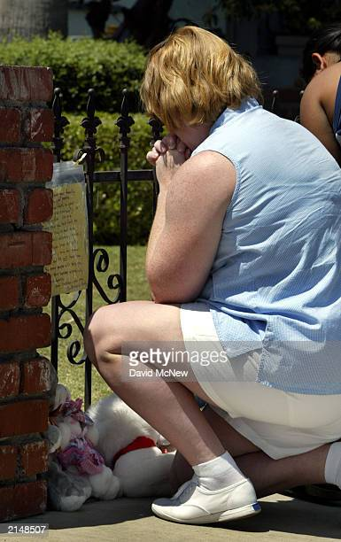 Lisa Behrends kneels in prayer as she adds items to a makeshift memorial at the house of a family of five found murdered July 9 2003 in Bakersfield...