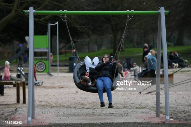 Lisa Beqiri and Dijarta Berisha on a swing at Victoria Park playground on March 6, 2021 in London, England. Londoners are enjoying bright weather as...