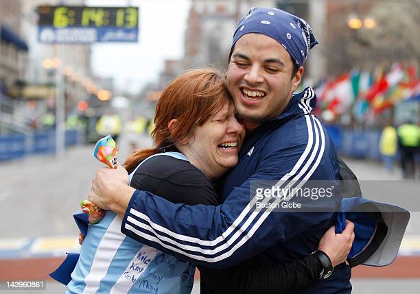 Lisa Burdick of Newton gets a hug from friend Harry Reyes who helped her run the final 6 miles of the Boston Marathon at the finish line Burdick was...