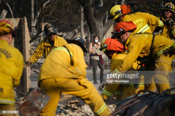Lisa Corwin, center, watches as firefighters search for a strongbox and a wedding ring through the remains of a neighbor's home in the Fountaingrove...
