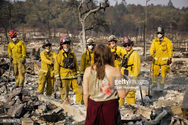 Lisa Corwin speaks to firefighters as they search for a strongbox and a wedding ring through the remains of a neighbor's home in the Fountaingrove...