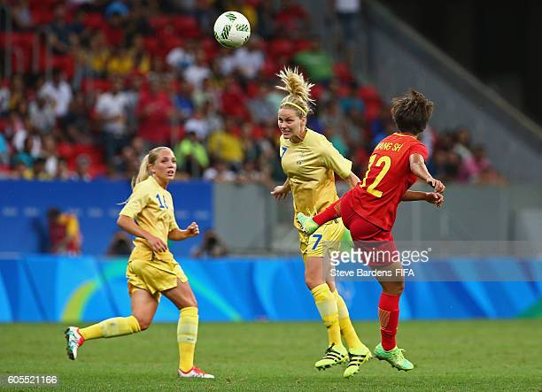 Lisa Dahlkvist of Sweden heads the ball away from Shuang Wang of China PR in action during the Women's First Round Group E match between China PR and...