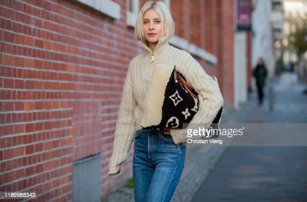 Lisa Hahnbück is seen wearing Louis Vuitton shearling teddy onthego GM tote bag Cult Gaia knit with zipper Citizens of Humanity flared denim jeans on...
