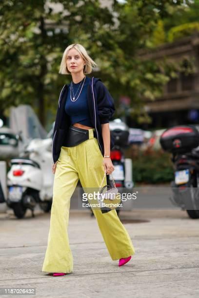 Lisa Hahnbück wears earrings necklaces a navy blue crop top a navy blue hooded sport jacket a black beltbag yellow corduroy widelegs full length...