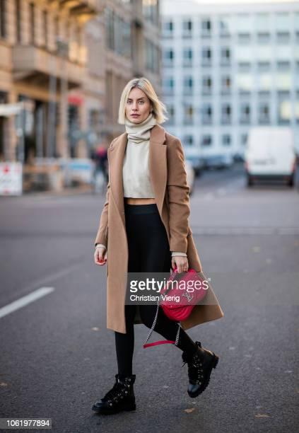 Lisa Hahnbueck is seen wearing brown coat Baum und Pferdgarten, Orse und Iris cropped turtleneck, red Louis Vuitton New Wave bag, Uniqlo x Alexander...