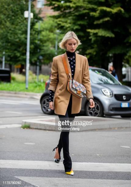 Lisa Hahnbueck is seen wearing Fendi bag, brown blazer, skinny pants with slit, two tone heels outside the Fendi show during Milan Fashion Week...