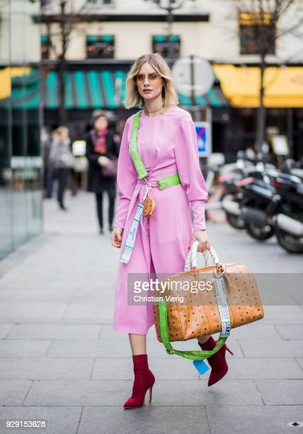 Lisa Hahnbueck is seen wearing pink Tibi dress red boots Gianvito Rossi weekender travel bag mini bag mcm x koenig souvenir during Paris Fashion Week...