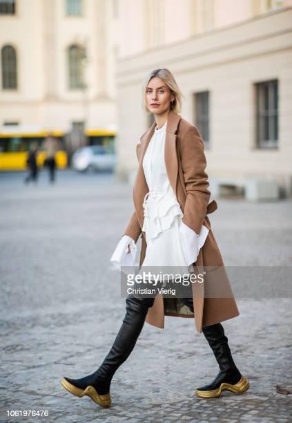Lisa Hahnbueck is seen wearing white dress with wide sleeves, black overknees boots Louis Vuitton Cruise 2018, brown coat Baum und Pferdgarten on...