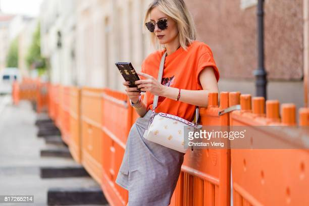Lisa Hahnbueck on the iphone with a Louis Vuitton phone case wearing an orange tshirt from Urban Outfitters with the print follow the Zeitgeist a...