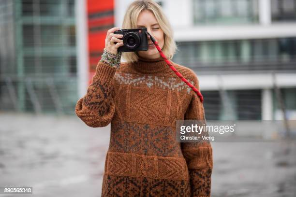 Lisa Hahnbueck taking a photo with her Leica camera wearing a brown knit Mulberry a brown Rochas dress golden Gianvito Rossi high heels on December...