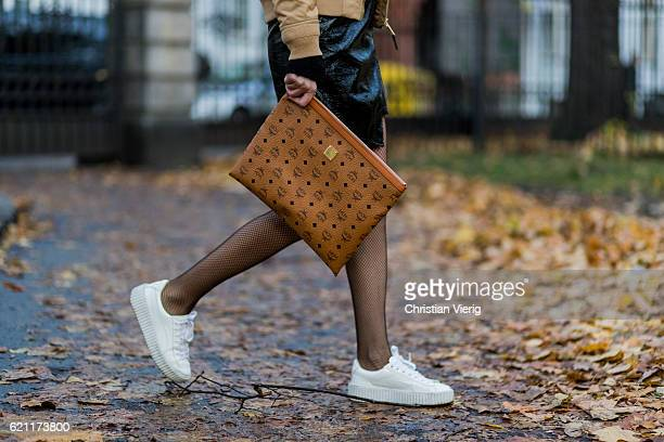 Lisa Hahnbueck wearing a beige Schott Bomber jacket a black Mango Asymmetric Patent leather skirt Fishnet tights white Puma Fenty Rihanna Creepers...