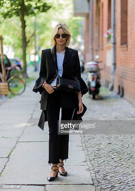 Lisa Hahnbueck wearing a black blazer from Ellery, J Brand jeans, Chanel bag and Christian Louboutin laced flats during the Mercedes-Benz Fashion...
