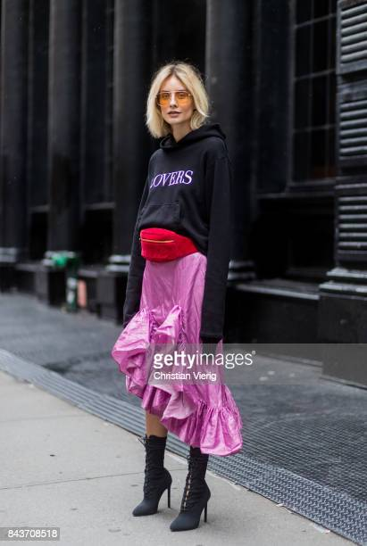 Lisa Hahnbueck wearing a black hoody with the print lovers red Gucci velvet belt bag pink ruffled skirt with slit black ankle boots vogue eyewear x...