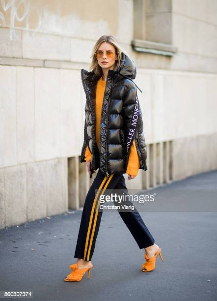 Lisa Hahnbueck wearing a black puffer jacket Moncler x Stylebop orange 81hours knit black Set pants with stripes orange Charlotte Olympia Bow Heels...
