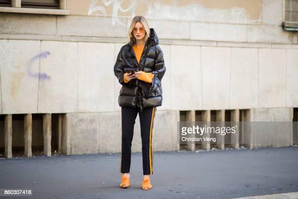 Lisa Hahnbueck wearing a black puffer jacket Moncler x Stylebop orange 81hours knit black Set pants with stripes orange Charlotte Olympia Bow Heels...