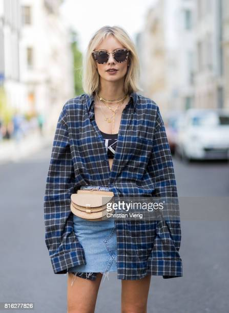 Lisa Hahnbueck wearing a checked Balenciaga men button shirt, a beige Chloe belt bag, a denim mini skirt, Dior ankle boots, sunglasses, a black...