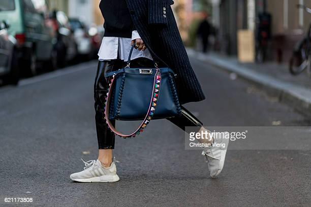 Lisa Hahnbueck wearing a navy white stripped Asos coat black hoody from Justin Bieber Merchandise Sweatshirt Purpose Tour an oversized white long...