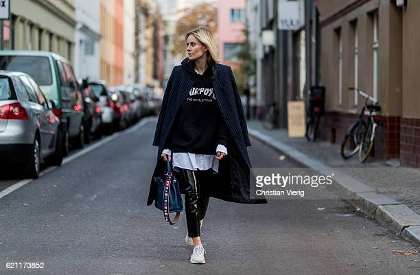Lisa Hahnbueck wearing a navy white stripped Asos coat black hoody from Justin Bieber Merchandise Sweatshirt Purpose Tour an oversized white long...