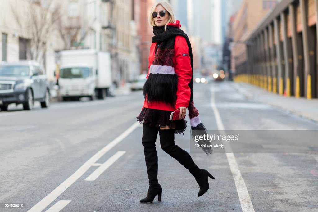 Lisa Hahnbueck wearing a red Tommy Hilfiger jacket, dress, black overknees, fake fur scarf on February 11, 2017 in New York City.