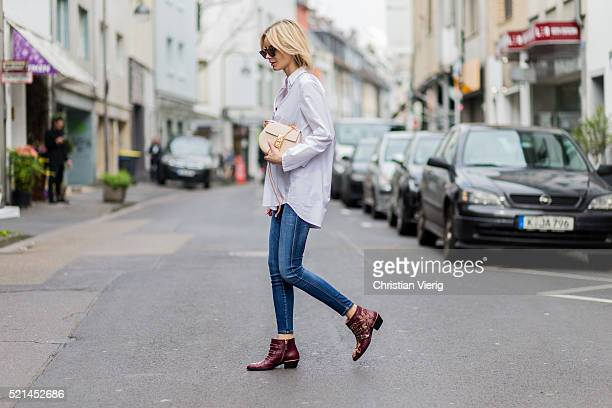 Lisa Hahnbueck wearing a white button shirt from Steffen Schraut blue denim jeans from Closed a creme bag and red Suzanna Studded Ankle Boot from...