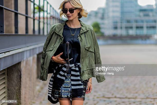 Lisa Hahnbueck wearing an olive jacket black shirt skirt and sweater from Marc Cain during the MercedesBenz Fashion Week Berlin Spring/Summer 2017 on...
