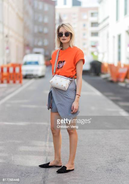 Lisa Hahnbueck wearing an orange tshirt from Urban Outfitters with the print follow the Zeitgeist, a grey plaid asymmetric skirt Storets a white...