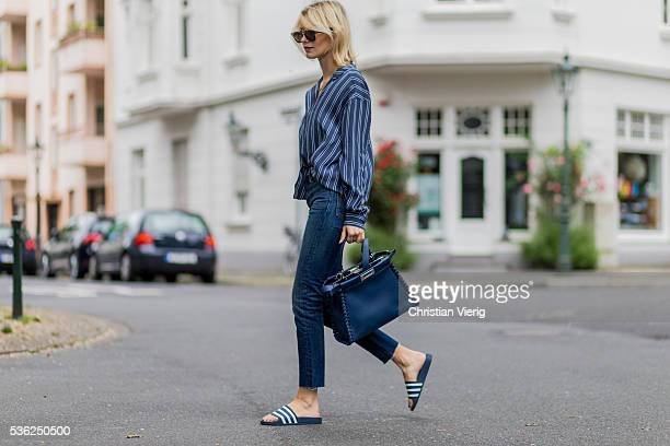 Lisa Hahnbueck wearing black Celine sunglasses a navy white striped Closed button shirt blue Fendi bag Levis denim jeans and Adidas bathing shoes on...