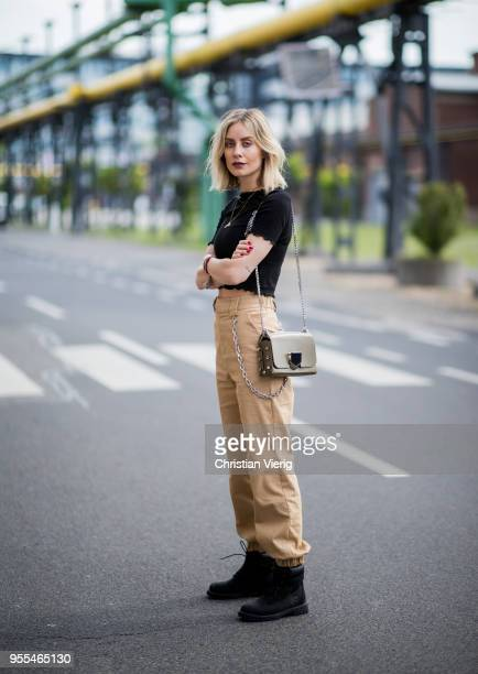 Lisa Hahnbueck wearing black cropped top HM beige IAMGIA cargo pants Timberland boots Jimmy Choo Lockett bag on May 3 2018 in Duesseldorf Germany