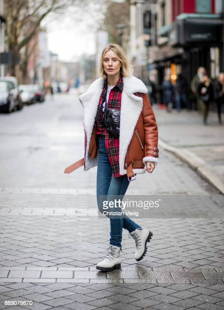 Lisa Hahnbueck wearing brown Acne Studios pistol leather jacket with inner lining, red checked Saint Laurent button shirt, blue J Brand jeans, white...
