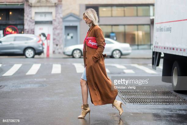 Lisa Hahnbueck wearing cropped denim shorts red Supreme x Louis Vuitton bag brown wool coat golden heels turtleneck on September 6 2017 in New York...
