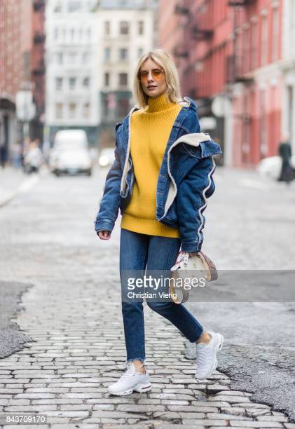 Lisa Hahnbueck wearing denim jacket yellow knit Fendi bag denim jeans white sneakers on September 6 2017 in New York City