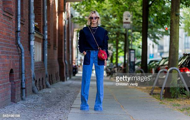 Lisa Hahnbueck wearing Fendi sunglasses wide leg denim pants a navy jumper from Victoria Beckham red Chloe bag and Guess heels during the...
