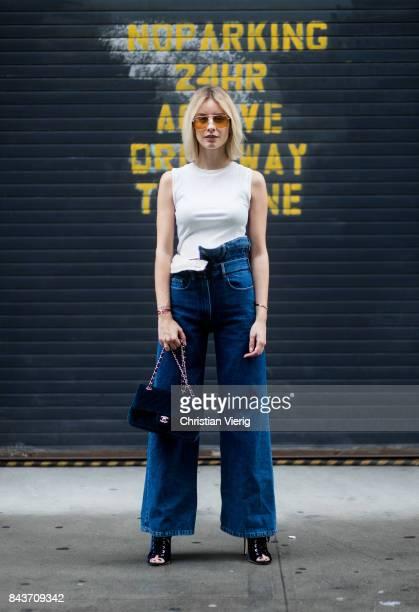 Lisa Hahnbueck wearing high waisted denim jeans white tshirt blue Chanel velvet bag on September 6 2017 in New York City