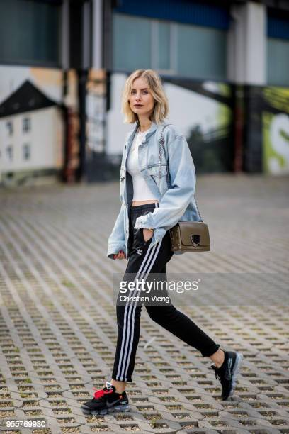 Lisa Hahnbueck wearing light blue Off White jeans jacket Gina Tricot cropped top black Adidas track pants nike paper max x off white sneaker olive...