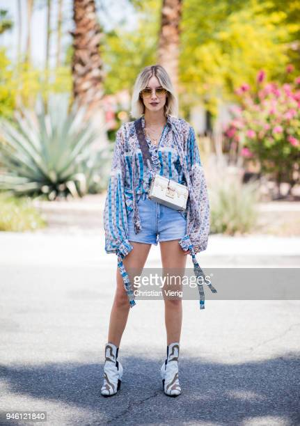 Lisa Hahnbueck wearing Louis Vuitton floral silk blouse, denim shorts, Louis Vuitton bag and boots, Gucci sunglasses is seen on April 13, 2018 in...