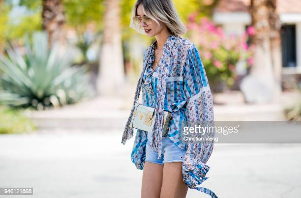 Lisa Hahnbueck wearing Louis Vuitton floral silk blouse denim shorts Louis Vuitton bag and boots Gucci sunglasses is seen on April 13 2018 in Indio...