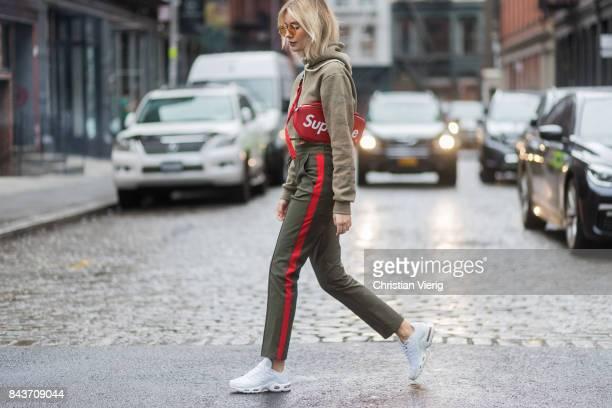 Lisa Hahnbueck wearing red Supreme x Louis Vuitton bag khaki hoody sweater pants with stripes sneakers vogue eyewear x Gigi Hadid sunglasses on...
