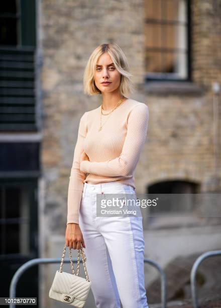 Lisa Hahnbueck wearing Samsoe & Samsoe knit, white Redone jeans, Chanel slippers, white Chanel bag seen during the Copenhagen Fashion Week...
