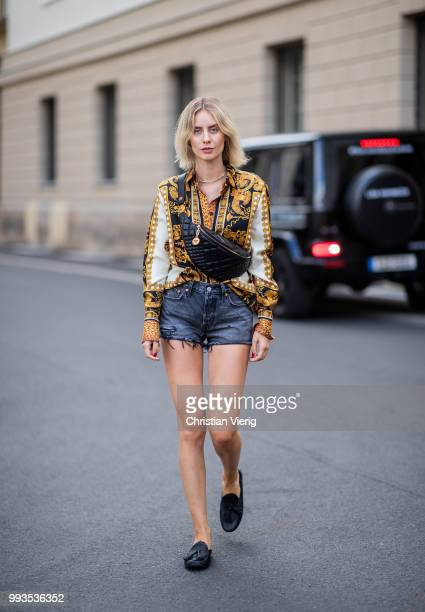 Lisa Hahnbueck wearing silk blouse with print Versace, Versace fanny belt bag , Levis 501 shorts, Tods loafer during the Berlin Fashion Week July...