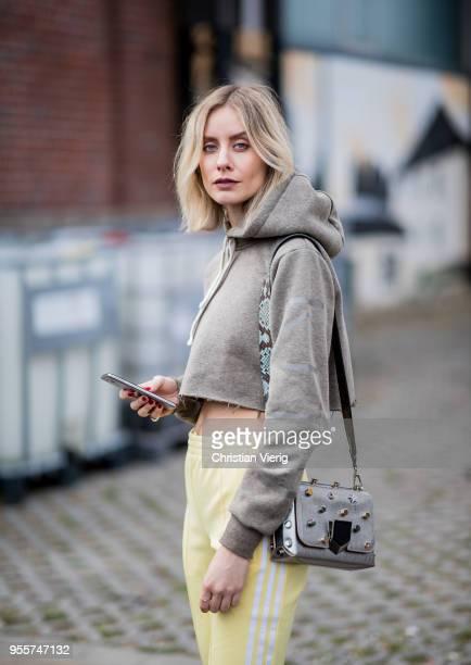 Lisa Hahnbueck wearing yellow Adidas track pants cropped hoodie kith olive Balenciaga knife boots Jimmy Choo Lockett bag on May 3 2018 in Duesseldorf...