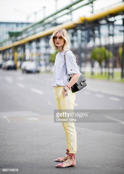Lisa Hahnbueck wearing yellow Adidas track pants oversized tshirt kith x champion Chanel bag Aquazzura pointed flats sunglasses on May 3 2018 in...