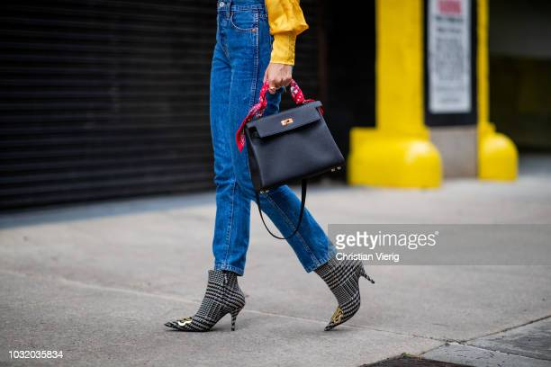 Lisa Hahnbueck wearing yellow wrapped silk blouse Revolve Levis jeans Re/done Balenciaga boots Hermes 28 Kelly bag is seen during New York Fashion...