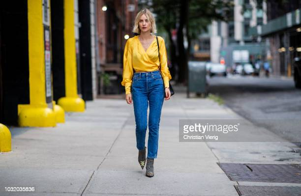 Lisa Hahnbueck wearing yellow wrapped silk blouse Revolve, Levis jeans Re/done, Balenciaga boots, Hermes 28 Kelly bag is seen during New York Fashion...