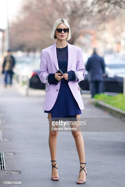 Lisa Hahnbueck wears sunglasses, a pale purple oversized long blazer jacket, a blue dress with a mesh part, shoes, outside BOSS, during Milan Fashion...