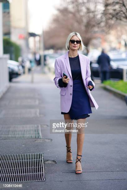 Lisa Hahnbueck wears sunglasses a pale purple oversized long blazer jacket a blue dress with a mesh part shoes outside BOSS during Milan Fashion Week...